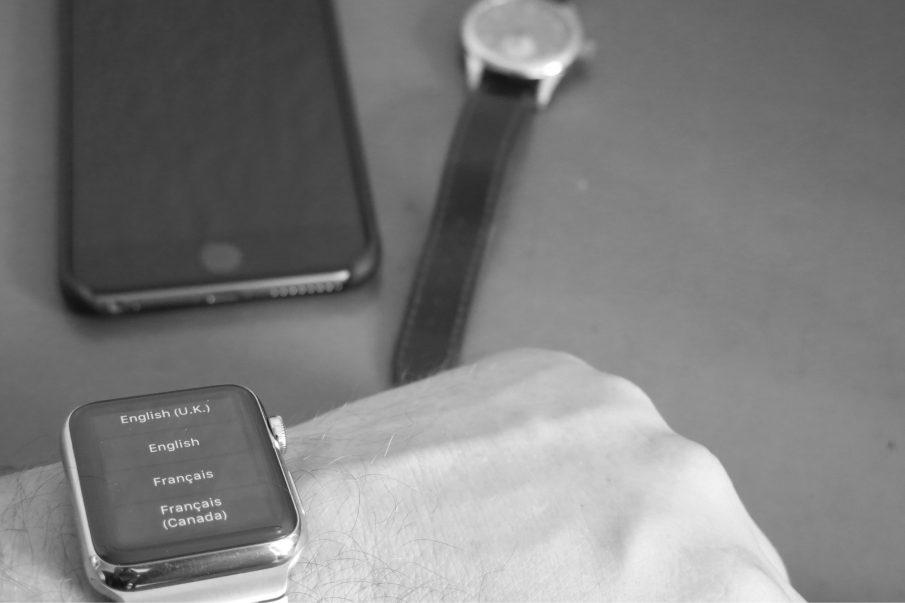 Watch am Handgelenk, im Hintergrund iPhone 6 Plus und Nomos Club